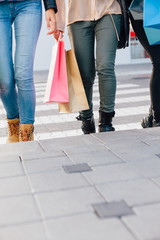 Closeup of three girls hold shopping bags and cross the street