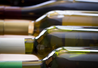 Wine bottles stacked on wooden racks shot with limited depth of