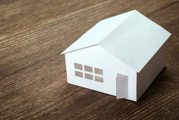 Paper house model on a wooden background. Selective focus.