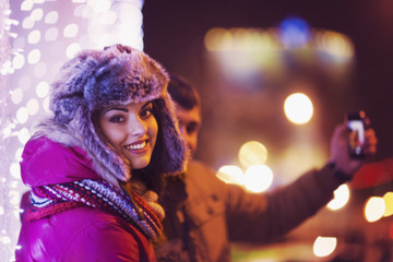 Couple making a selfie with a christmas tree at background
