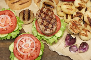 Picnic Table Top With BBQ Grilled Burgers And Vegetables