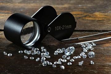 geschliffene Diamanten mit Einschlaglupe auf rustikalem Holzhintergrund