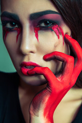 portrait of freak monster with mess dirty colored makeup on her face. crying woman with red bloody tears and hand. halloween concept on green background. studio shot, dark brown eyes.