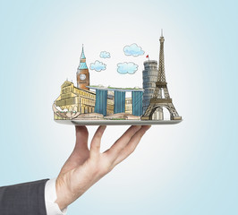 A man's hand holds a tablet with sketches of the most famous places in Italy, Great Britain, France and Singapore. The concept of tourism and sightseeing. Light blue background.