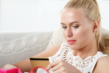 Beautiful blonde woman holding and examining golden credit card