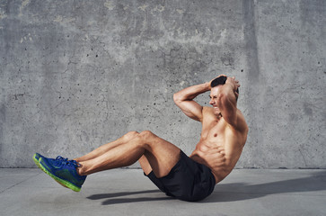 Fitness model exercising sit ups and crunches