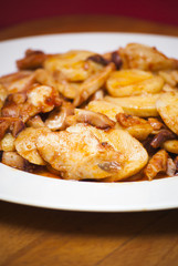 Octopus with paprika and potatoes on a white plate, also known a