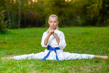 girl in white kimono during training karate exercises at summer