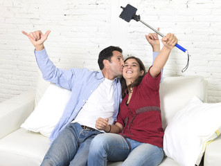 attractive couple taking selfie photo or shooting self video with mobile phone and stick sitting at home couch smiling happy
