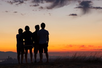Four people silhouettes on top of hill during sunset