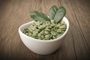 Wall Mural - White bowl with green coffee beans on the wood