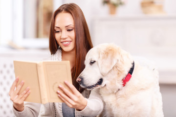 Young lady showing a book to her pet.