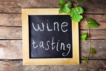 Old square chalk scripted frame with vine on wooden background