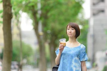 アイスコーヒーを持って歩く女性