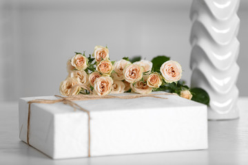 Big white gift box with bouquet of roses on the table