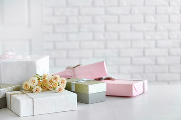 Decorated gift boxes and bouquet of roses on white brick wall background