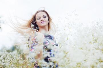 Beauty Girl enjoying nature, blond girl in dress  on a meadow