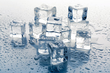 Melting ice cubes on grey background, close up