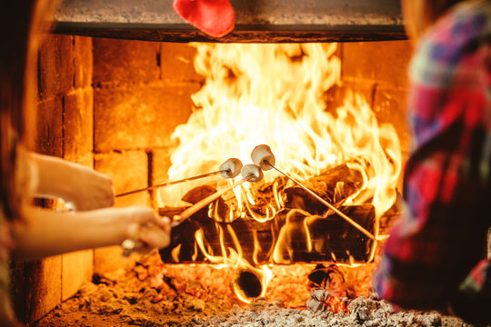 Family roasting marshmallows by the fire. Cozy chalet home with fireplace decorated with traditional Christmas ornaments. Cozy relaxed magical atmosphere in a chalet. Holiday concept.