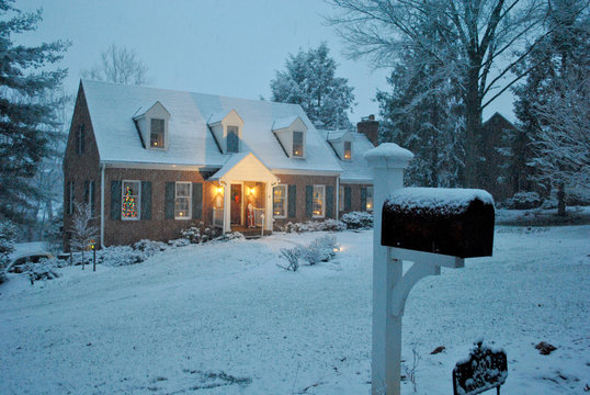 Cozy Williamsburg-style house in the snow on a winter evening in December during the Christmas/Holiday Season