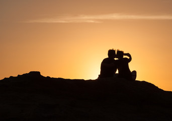 Silhouette of Couple sitting on a rock near the sea and watching the sunset