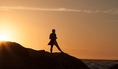 Silhouette of a woman standing in front of the sunset at the California shoreline.