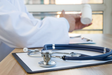 Close-up of stethoscope and folder on background of doctors at work