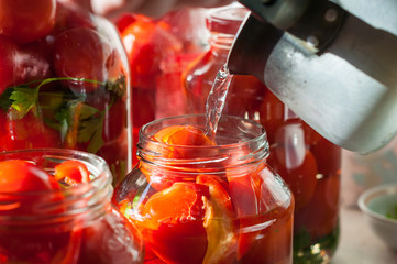 Canning process of tomato in mason jar. On background is few