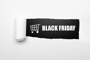 Shopping cart and black friday text on paper tear