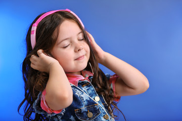 Happy little girl in jeans T-shirt listen music with pink headphones on blue background