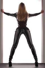 Frau mit langen Beinen im schwarzen Catsuit Latexanzug