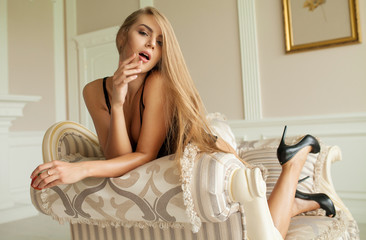 Beautiful sexy lady in elegant black panties and stockings. Portrait of fashion model girl indoors. Beauty blonde woman with attractive buttocks in lace lingerie. Female ass in underwear