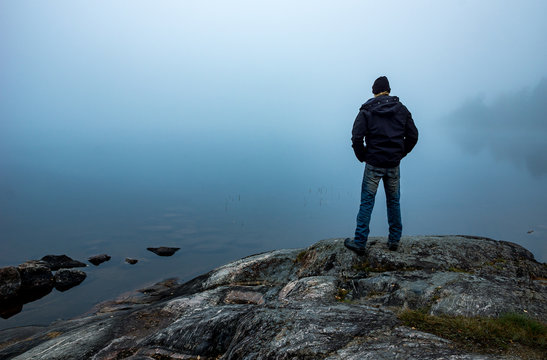 Man standing on cliff looking out over fog covered lake