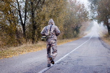 Backview of man in camouflage running on autumn countryside road