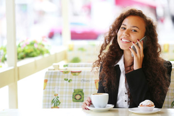 Young smiling woman speaking by cellphone in the restaurant