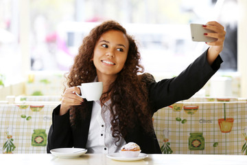 Young smiling woman with cup of coffee takes selfie at the restaurant's terrace
