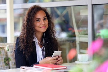 Young business woman listens music at the restaurant