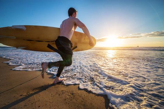Surfer running into the ocean