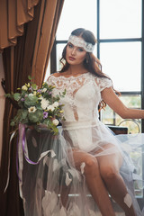 Beautiful bride with long hair in boudoir dress