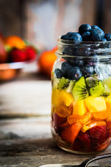 Colorful fruit salad in a jar on rustic wooden background