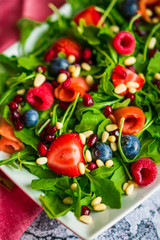 Healthy salad with arugula,spinach,smoked salmon and berries