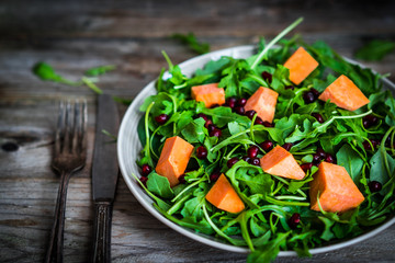 Wall Mural - Fresh arugula and spinach salad with pumpkin on rustic backgroun