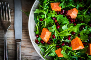 Fresh arugula and spinach salad with pumpkin on rustic backgroun