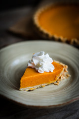 Pumpkin pie on rustic wooden background