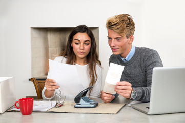 Man and woman at a kitchen table, sorting out their personal fin