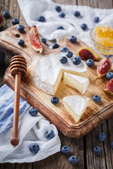 Brie cheese,Camembert with Ingram,blueberries and honey on a wooden Board.selective focus
