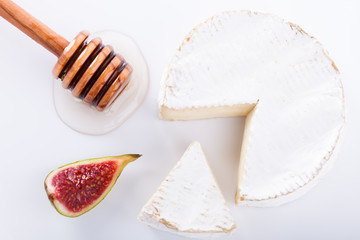 Brie cheese on with a white background with fresh figs and honey.selective focus.