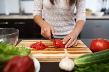 girl chops tomato on salad in the kitchen
