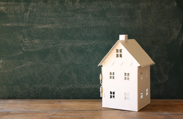 miniature toy house over chalkboard background. room for text