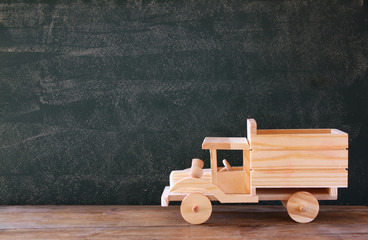 photo of wooden toy truck in front of chalkboard